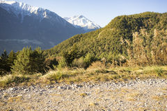 Mountain landscape with snowy peaks. Scenic mountain landscape background with snowy peaks and forested slopes in autumn or early winter Stock Images