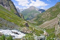 Mountain landscape, a stream and small lake. Kyrgyzstan Royalty Free Stock Photos