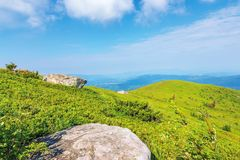 Mountain landscape on summer morning. Meadows on the hills decorated with big white sharp rocks. beautiful green and blue nature scenery on a sunny day royalty free stock photography