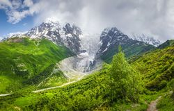 Mountain landscape on sunny summer day. Mount Tetnuldi and glacier Lardaad. Svaneti mountains and green hills Royalty Free Stock Photography