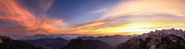 Mountain landscape at sunset in Julian Alps. Amazing view on colorful clouds and layered mountains. Stock Photos