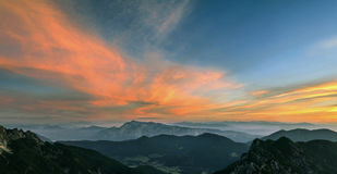 Mountain landscape at sunset in Julian Alps. Amazing view on colorful clouds and layered mountains. Stock Photo