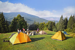 Mountain landscape at sunshine. Tourist tents in forest Stock Photos