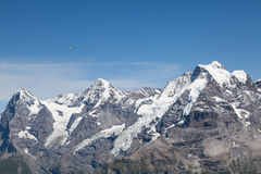 Mountain Landscape. In the Swiss Alps with a small plain flying. View from Mt. Schilthorn Royalty Free Stock Image