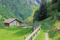 Mountain landscape in Switzerland with walking path and cabin. Mountain landscape with high mountains in Switzerland with open field, walking path and cabin royalty free stock photos