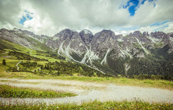 Mountain landscape with trail, green meadow and forest Stock Photo