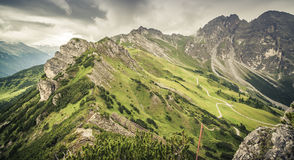 Mountain landscape with trail, green meadow and forest Royalty Free Stock Image