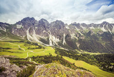 Mountain landscape with trail, green meadow and forest Royalty Free Stock Images