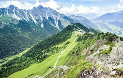 Mountain landscape with trail, green meadow and forest Royalty Free Stock Photos
