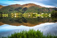 Mountain Landscape with A Tranquil Village, Green Forest and Lake Reflection in Summer royalty free stock images
