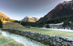 Mountain landscape and valley with forest and snow-capped mountain peaks and an old rock wall with wooden huts and chalets behind. In the Sardasca Valley near royalty free stock photography
