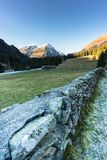 Mountain landscape and valley with forest and snow-capped mountain peaks and an old rock wall with wooden huts and chalets behind. In the Sardasca Valley near royalty free stock photos