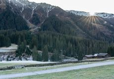 Mountain landscape and valley with forest and snow-capped mountain peaks and an old rock wall with wooden huts and chalets behind. In the Sardasca Valley near royalty free stock image
