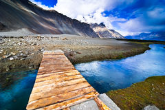 Mountain landscape view with river. And wooden bridge over evening blue sky. India, Ladakh, Nubra Valley Royalty Free Stock Photo