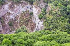 Mountain landscape waterfall flows down the cliff. Royalty Free Stock Photography