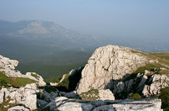 The mountain landscape with white limestone rocks and distant mountains in gauze. The mountain landscape with white limestone rocks covered by savin and distant Royalty Free Stock Image