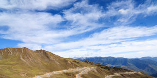 Mountain landscape with white sutra streamer scattered on the gr Royalty Free Stock Image