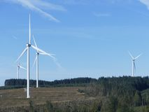 Mountain landscape  of Wind turbines power. Mountain landscape of Fore large wind turbines set in lush green  Welsh forest with bright blue sky Royalty Free Stock Photos