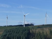 Mountain landscape  of Wind turbines power. Mountain landscape of Four large wind turbines set in lush green  Welsh forest with bright blue sky Royalty Free Stock Photography