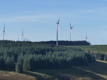 Mountain landscape  of Wind turbines power. Mountain landscape of Six large wind turbines set in lush green forest with bright blue sky Royalty Free Stock Image