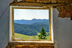 Mountain landscape through the window of an abandoned house. Selective focus Stock Photo