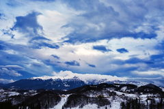 Mountain landscape in winter with cloudy sky Stock Images