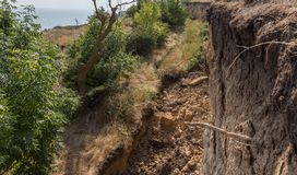 Mountain landslide disaster in sesmically dangerous area. Large cracks in earth, descent of large layers of earth blocking road. M. Ortal danger of damming royalty free stock images