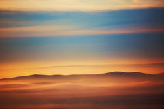 Mountain layer in morning sun ray and winter fog. Royalty Free Stock Images