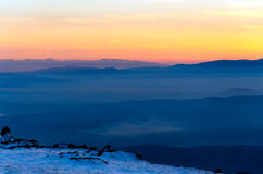 Mountain layers and colorful sunset in wintry mountain. Golden sky and stunning sunset in wintry mountain, romantic background for postcard or wallpaper Royalty Free Stock Photo
