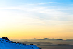 Mountain layers and colorful sunset in wintry mountain. Golden sky and stunning sunset in wintry mountain, romantic background for postcard or wallpaper Stock Photos