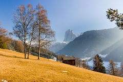 Mountain lodge in valley of pine forests and snow-capped peaks i Royalty Free Stock Photos