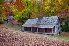 Mountain log cabin with long front porch and barn stock photography