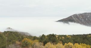 Mountain with a lot of mist in autumn. Ascending movement over mountain with a lot of mist in autumn stock video footage