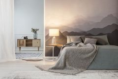 Mountain lover`s open space bedroom. Illuminated mountain lover`s open space bedroom interior with a wooden cabinet and a gray cozy bed against a landscape stock image