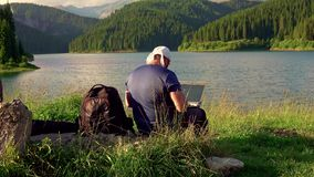 Mountain man working with laptop in the mountains stock footage