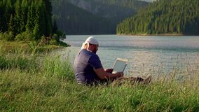 Mountain man working with laptop in the mountains stock video footage