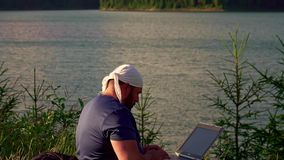 Mountain man working with laptop in the mountains stock video