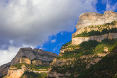 Mountain massife grey and yellow rock with green trees under blu Royalty Free Stock Image