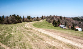 Mountain meadow with hiking trail, few houses, forest and clear sky in Slovakia Stock Photography