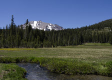 Mountain Meadow with a Stream Against Blue Sky Stock Photography