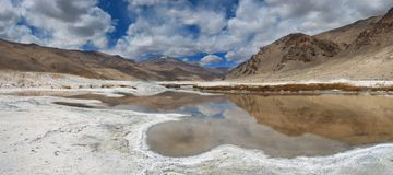 Mountain mineralized lake, wavy line of salt beach, in the water reflect the mountains, panorama, the Himalayas. Mountain mineralized lake, wavy line of salt Royalty Free Stock Image