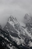 Mountain in the mist. The Grand Teton peaks through the clouds within Grand Teton National Park Stock Photos