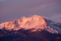 Mountain Morning. As the sun rises over a snow capped mountain the summit contrasts a winter sky Royalty Free Stock Photos
