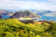 Mountain morraine lake under blue sky. Mountain morraine lake and green rocks under blue sky Royalty Free Stock Photo