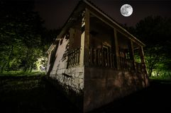 Mountain night landscape of building at forest in foggy night with moon. Green meadow, big trees and abandoned house at night. Nig. Mountain night landscape of royalty free stock image