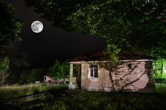 Mountain night landscape of building at forest in foggy night with moon. Green meadow, big trees and abandoned house at night. Nig. Mountain night landscape of stock photos