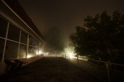Mountain night landscape of building at forest in foggy night with moon. Green meadow, big trees and abandoned house at night. Nig. Mountain night landscape of royalty free stock photography