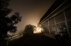 Mountain night landscape of building at forest in foggy night with moon. Green meadow, big trees and abandoned house at night. Nig. Mountain night landscape of stock photography