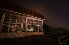 Mountain night landscape of building at forest in foggy night with moon. Green meadow, big trees and abandoned house at night. Nig. Mountain night landscape of royalty free stock photos