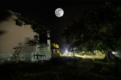 Mountain night landscape of building at forest in foggy night with moon. Green meadow, big trees and abandoned house at night. Nig. Mountain night landscape of royalty free stock images